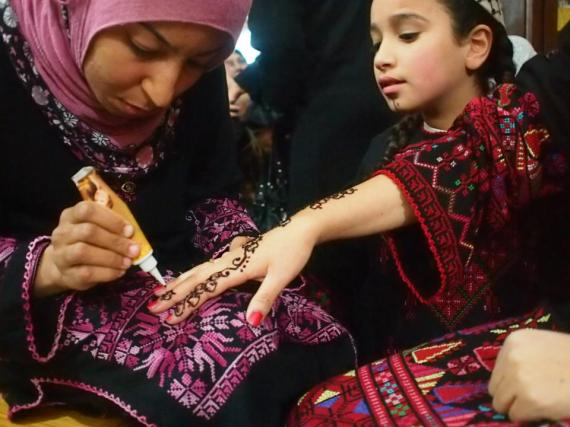 The bride is getting a Henna painting on her hand