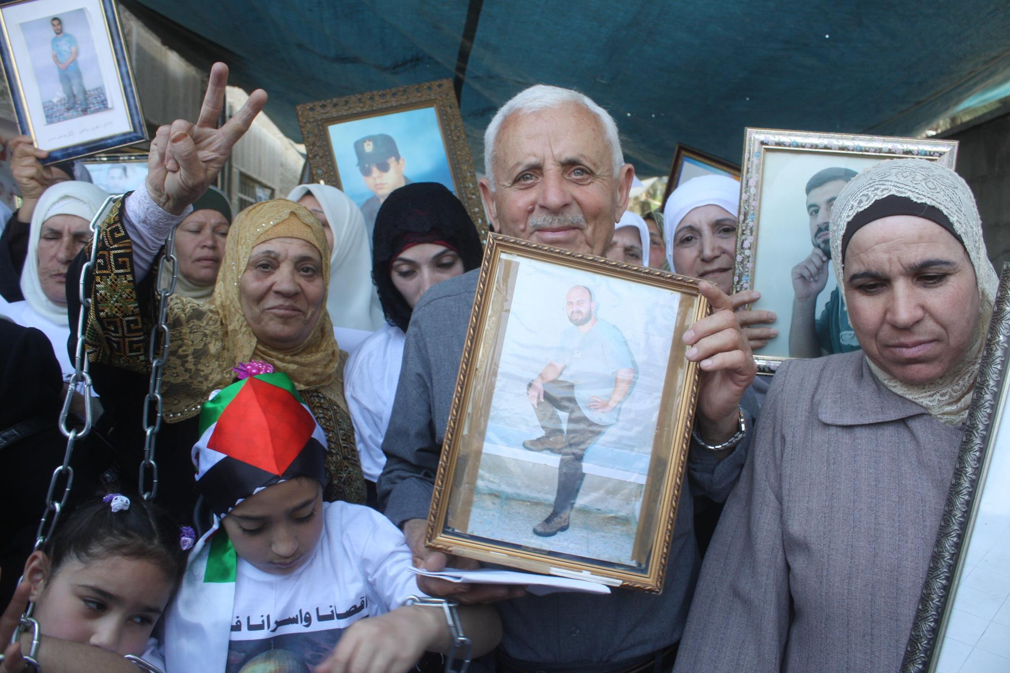 Jihad's father, holding Jihad's picture, celebrates his son's upcoming release from Israeli prison. (Amjad Abu Asab)