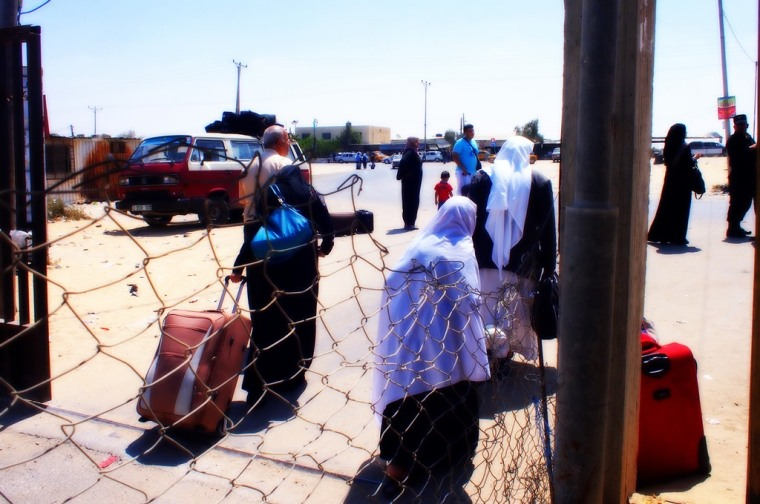Palestinian elderly people dragging their luggage and returning back home after hearing of the closure of Rafah border